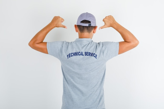 Hombre de servicio técnico que muestra texto en uniforme en camiseta gris con gorra
