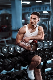 Un hombre sexualmente entrenado bebe nutrición deportiva después de un entrenamiento fuerte, manos, pies, espalda, bíceps y tríceps