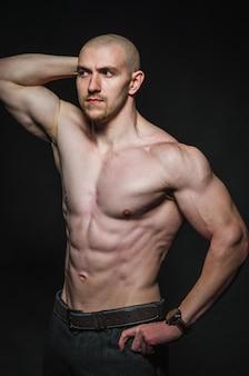 Hombre sexy deportivo se encuentra en topless en la oscuridad. deportes, belleza.