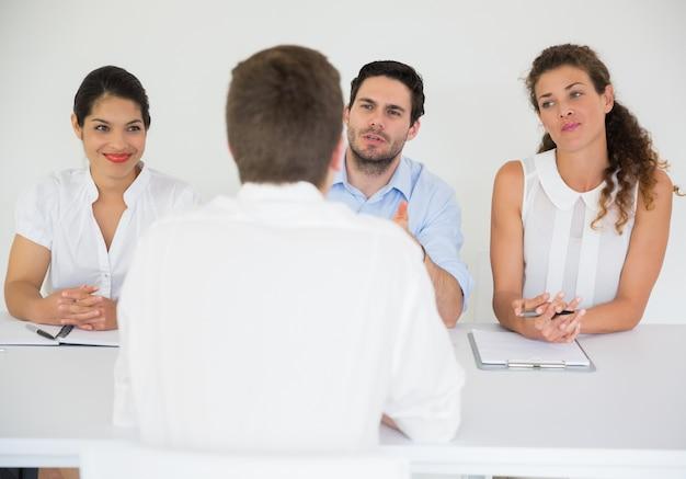 Hombre siendo entrevistado por gente de negocios