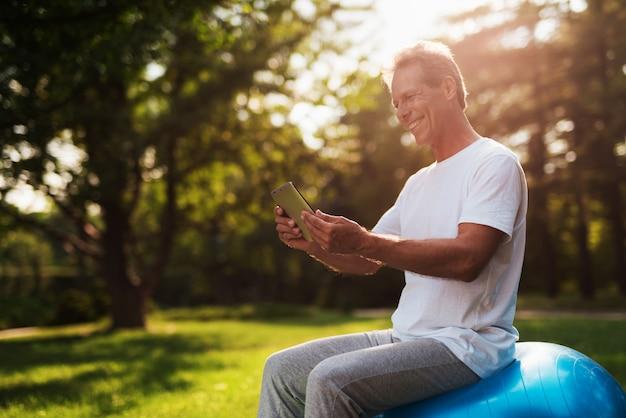 El hombre se sienta en la bola para yoga y mira en su tableta