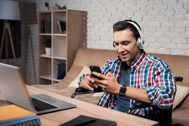 Un hombre se sienta en casa y escucha música con auriculares.