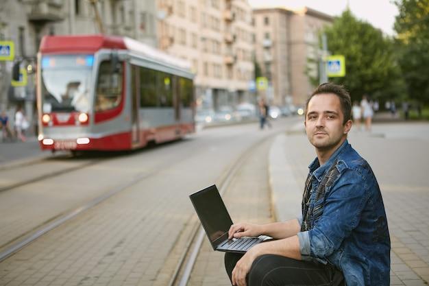 Un hombre se sienta cerca de la línea del tranvía con una computadora portátil en su regazo.