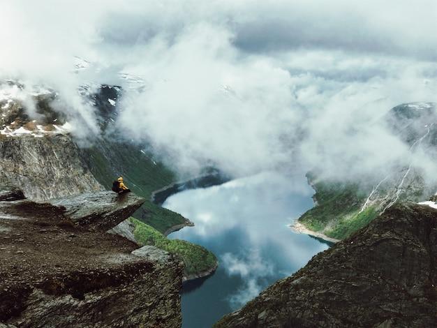 El hombre se sienta en el extremo de trolltunga antes de las montañas