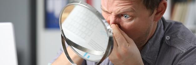 El hombre se sienta frente al espejo y presiona su cara