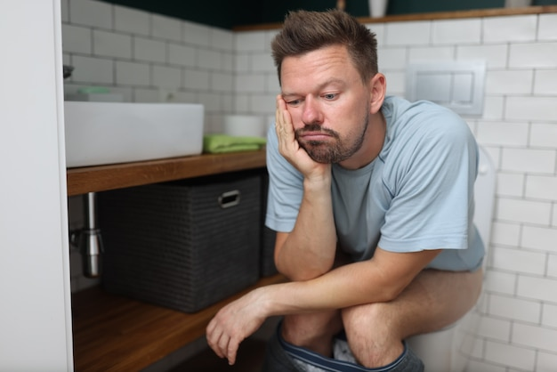 El hombre se sienta en el inodoro con estreñimiento y espera a que surta efecto el laxante.