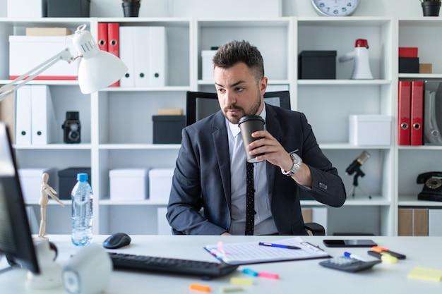 Un hombre se sienta en la oficina a la mesa, toma café y mira el monitor de la computadora.