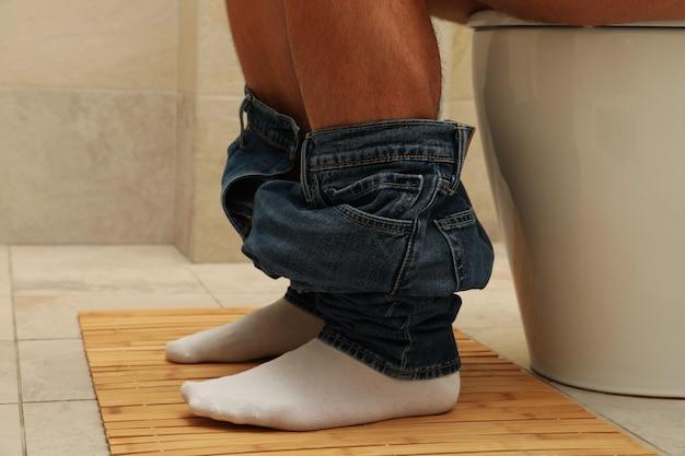 Un hombre se sienta con los pantalones bajados en el inodoro.