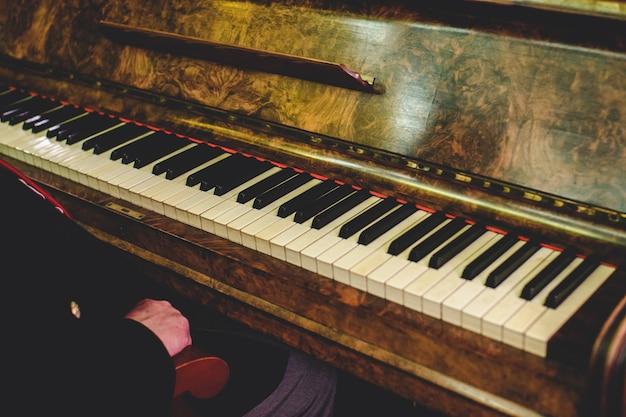 El hombre se sienta en un viejo piano de época