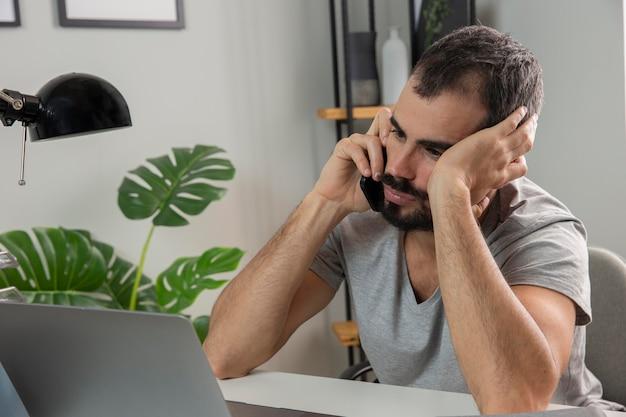 El hombre se siente cansado mientras trabaja desde casa y habla por teléfono