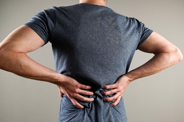 El hombre siente dolor en la parte baja de la espalda.