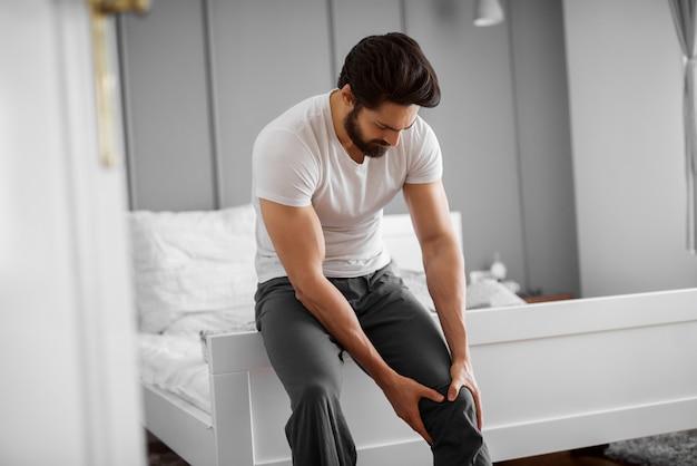 El hombre siente dolor en la rodilla.