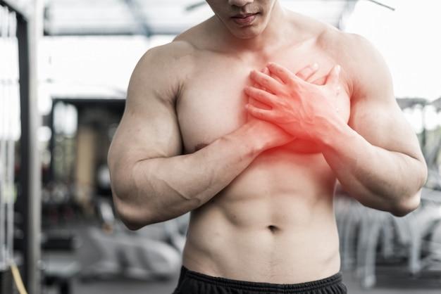 Hombre siente dolor en su corazón mientras trabaja en la oficina, concepto médico