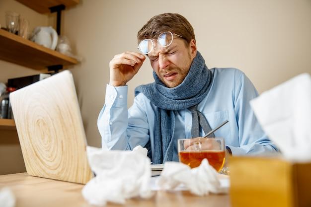 El hombre se siente enfermo y cansado. hombre con taza trabajando en casa, empresario resfriado, gripe estacional.