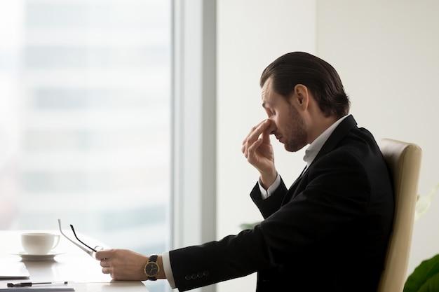El hombre siente fatiga en los ojos después de trabajar en la oficina