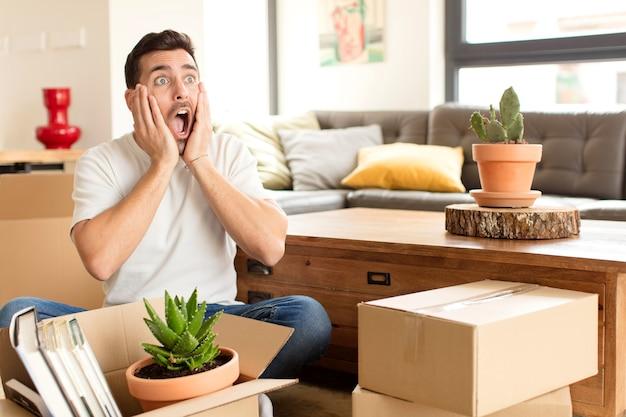 El hombre se siente feliz, emocionado y sorprendido, el hombre mirando hacia un lado con ambas manos en la cara.