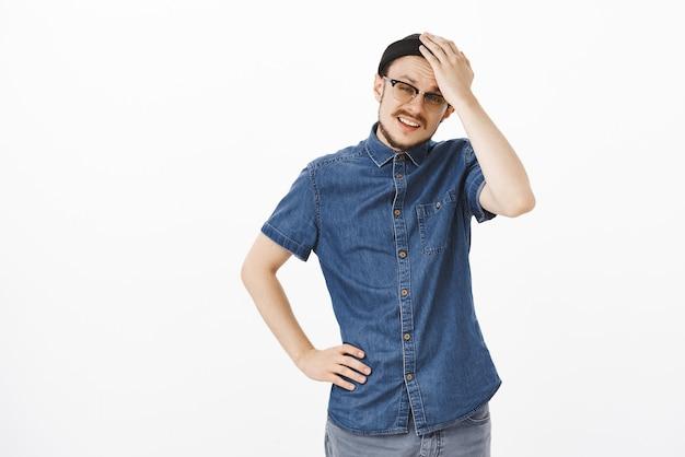 El hombre se siente molesto y disgustado recibiendo trabajo extra frotándose la frente levantando las cejas y sosteniendo la mano en la cintura mirando preocupado y perezoso con gorro negro sobre una pared gris