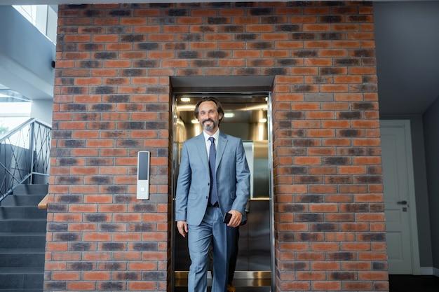 El hombre se siente motivado. empresario de pelo gris con traje y corbata sintiéndose motivado antes de la reunión