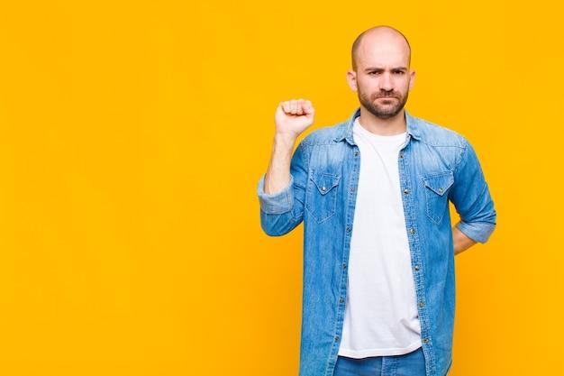 El hombre se siente serio, fuerte y rebelde, levantando el puño