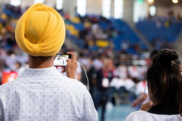 Hombre sij indio turbante de cabeza amarilla vuelta atrás vista usar teléfono inteligente para grabar la competencia deportiva de filmación