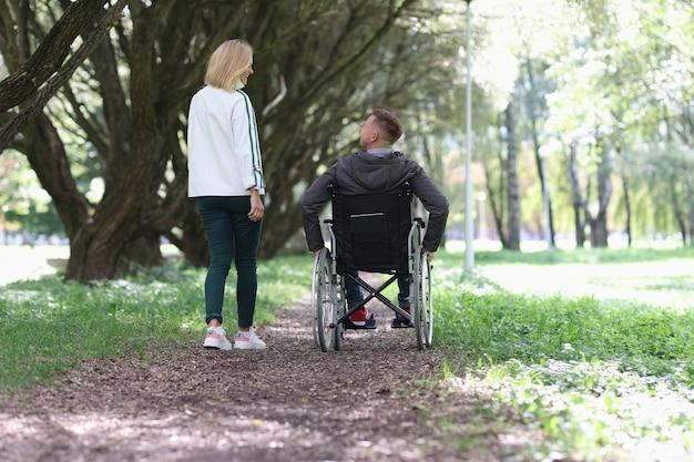 Hombre en silla de ruedas está caminando en el parque con su novia estrechas relaciones entre personas con