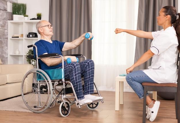 Hombre en silla de ruedas haciendo ejercicio con mancuernas para la recuperación.