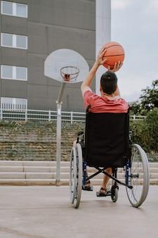 Un hombre en silla de ruedas juega baloncesto