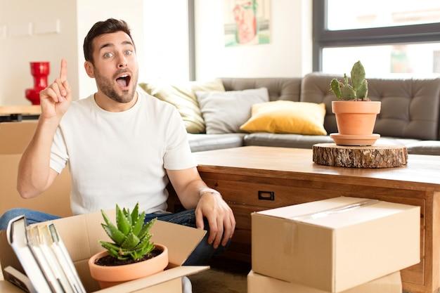 Hombre sintiéndose como un genio feliz y emocionado después de darse cuenta de una idea, levantando alegremente el dedo, ¡eureka!
