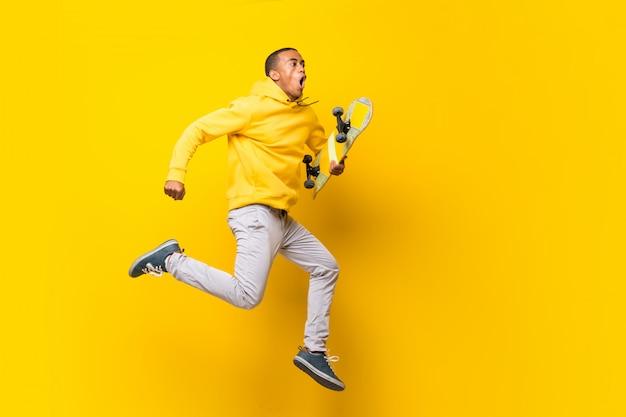 Hombre skater afroamericano sobre blanco aislado