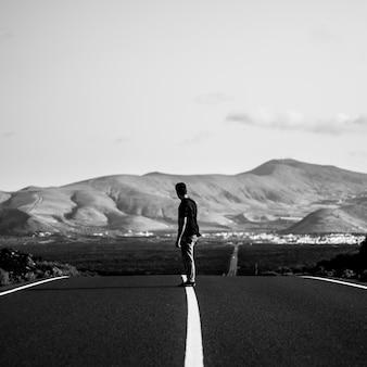 Hombre en un skater cabalgando sobre una carretera vacía con colinas increíbles