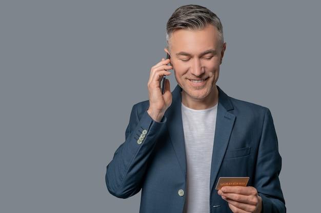Hombre con smartphone cerca de la oreja mirando tarjeta de crédito