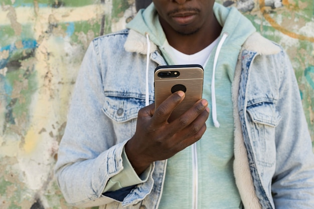 Hombre con smartphone enfrente de muro