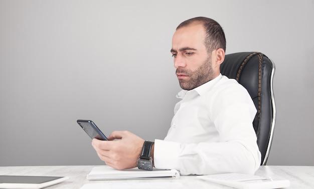 Hombre con smartphone. escritorio de oficina moderno. tecnología