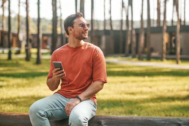 Hombre con smartphone mirando al lado