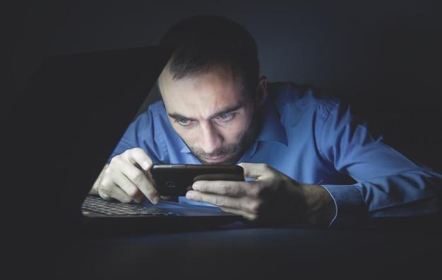 Hombre con smartphone por la noche. tecnología. negocio