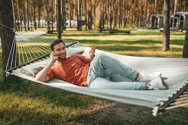 Hombre con smartphone relajante en hamaca