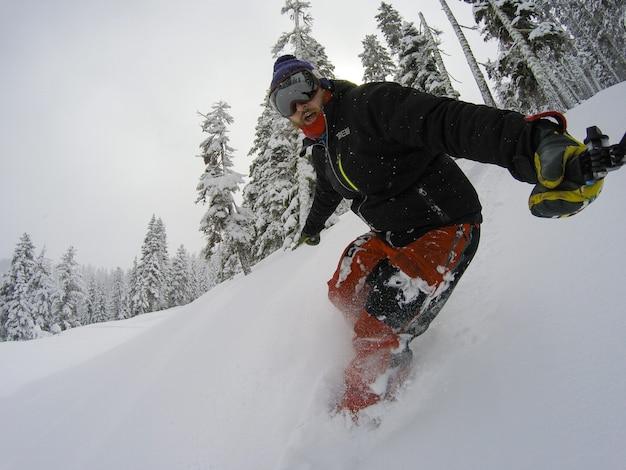 Hombre de snowboarder tomando selfie en acción