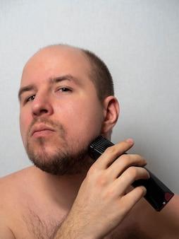 Un hombre sobre un fondo gris se afeita la barba con una maquinilla de afeitar eléctrica.
