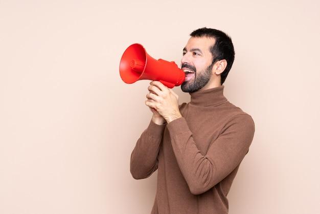 Hombre sobre pared aislada gritando a través de un megáfono