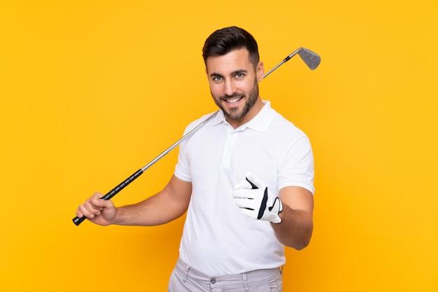 Hombre sobre pared amarilla aislada jugando al golf y apuntando hacia el frente