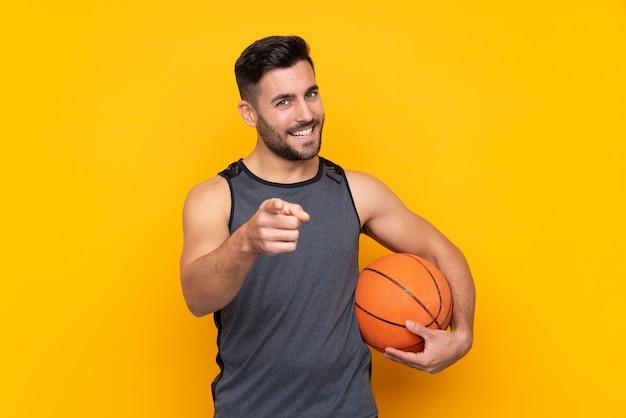 Hombre sobre pared amarilla aislada jugando baloncesto y apuntando hacia el frente