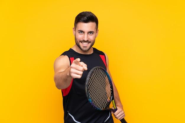 Hombre sobre pared amarilla aislada jugando tenis y apuntando hacia el frente