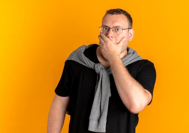 Hombre con sobrepeso en gafas con camiseta negra cubriendo la boca con la mano sorprendida por naranja