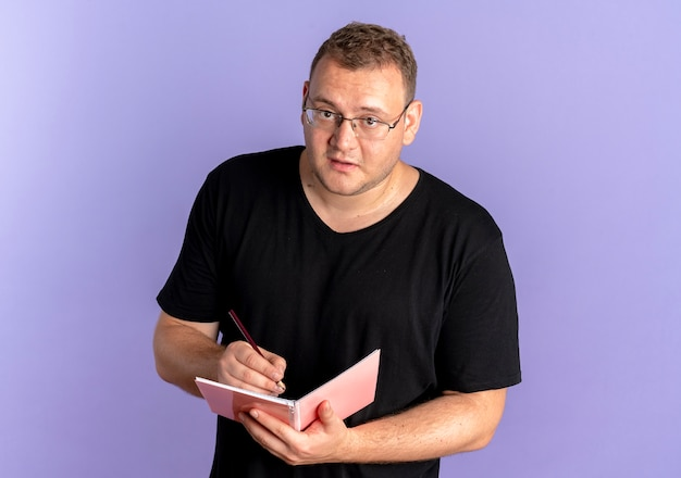 Hombre con sobrepeso en gafas con camiseta negra sosteniendo el cuaderno escribiendo algo con cara seria sobre azul