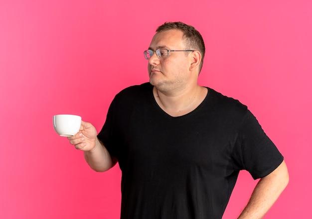 Hombre con sobrepeso en gafas con camiseta negra sosteniendo la taza de café mirando a un lado con cara seria sobre rosa