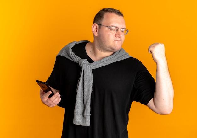 Hombre con sobrepeso en gafas vistiendo camiseta negra con smartphone golpeando el puño regocijándose de su éxito sobre naranja