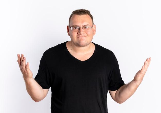 Hombre con sobrepeso vestido con camiseta negra con gafas mirando confundido extendiendo los brazos hacia los lados de pie sobre la pared blanca