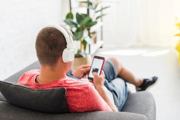 Hombre en el sofá ve una película en el teléfono móvil con auriculares