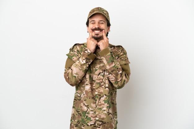 Hombre soldado aislado sobre fondo blanco sonriendo con una expresión feliz y agradable