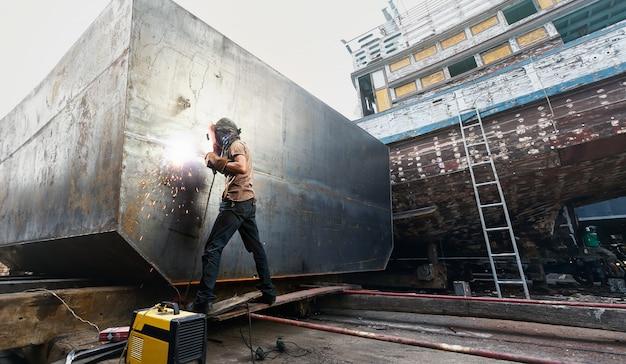 Hombre soldador trabajando en el astillero local.